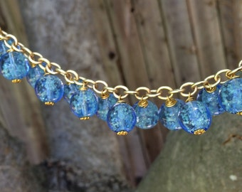 Blue glow in the dark beaded bracelet with gold chain.