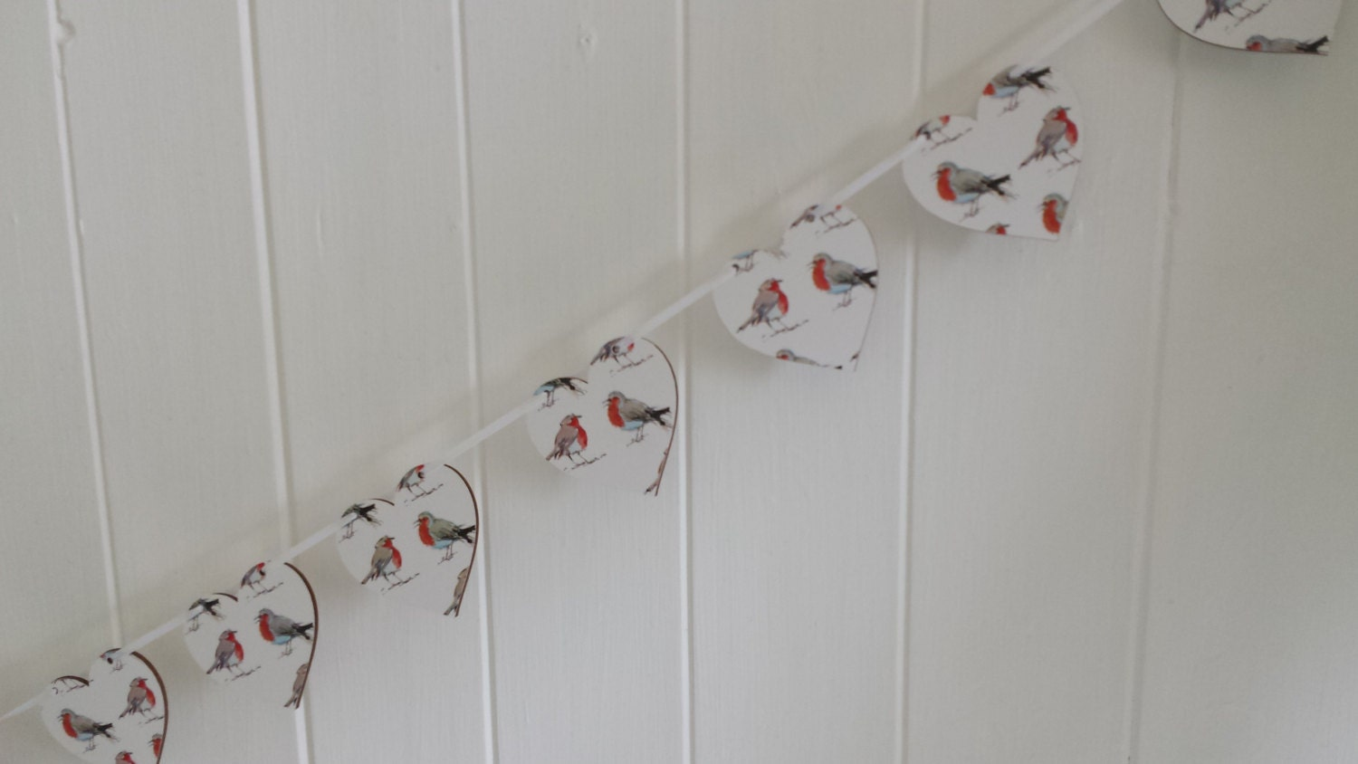 Hand made decoupaged wooden heart Christmas bunting featuring cheeky festive robins on a white background