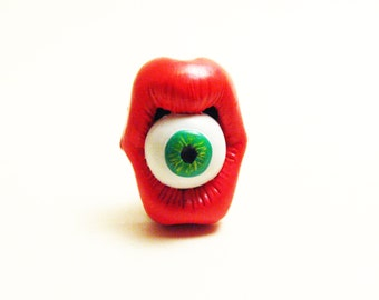 Mouth and eye green lapel pin