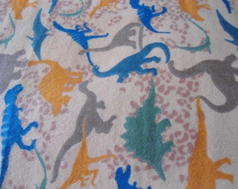 Burp cloth with green, blue, brown orange dinosaurs on tan back ground.