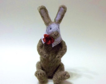 Ash Is A Primitive Needle Felted Bunny Wearing A White Collar and Cinnamon Bow