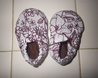 white crib shoes with brown line drawn flowers