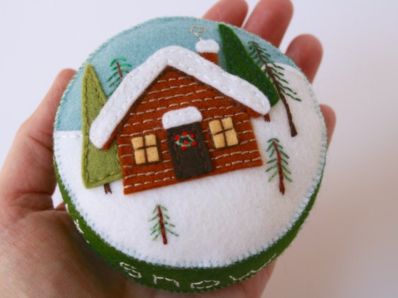 wool felt pincushion with a little log cabin in the snowy woods