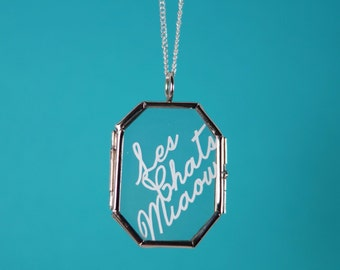 "Handcut papercut ""Les chats miaow"" necklace, encased in a glass locket."