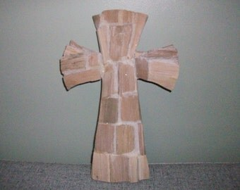Driftwood cross with white beach sand