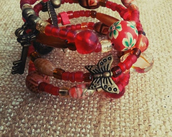 Boho cuff. Seed beads, Czech glass, fimo, wood in shades of red. Antique brass charms