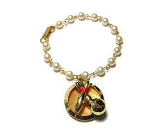 Pearl bowling bracelet, creamy white faux pearl chain with a charm of two bowling pins and a bowling ball, black and red enamel accents