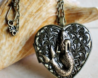 Mermaid music box locket, heart shaped locket with music box inside, in bronze with mermaid on front cover.
