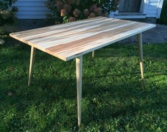 Mid century modern dining table featuring wormy maple with tapered wood legs.