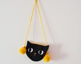 Cute black cat bag and honey yellow pompoms.