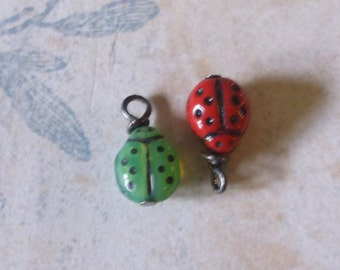 Green or red lady bug charms..Gun metal color bails 10 each