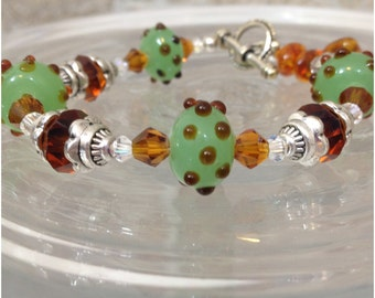 Silver tone bracelet with green and brown lampwork beads and brown crystals