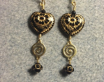 Black with gold inlay Czech glass heart bead dangle earrings adorned with gold swirly links and black Saturn beads.