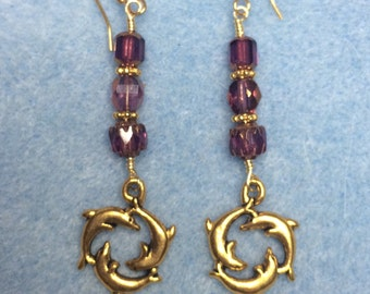 Gold circle dolphin charm dangle earrings adorned with purple Czech glass beads.