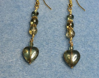 Olive green Czech glass heart dangle earrings adorned with green Czech glass beads.