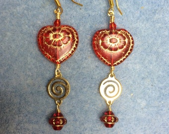 Red with gold inlay Czech glass heart dangle earrings adorned with gold swirly link and red Saturn beads.
