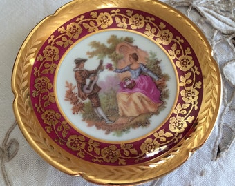 """Limoges La Reine Collectable Miniature 3 1/4"""" Decorative Plate/Pin/Trinket Dish.  Fragonard Courting Couple.  Maroon with Thick Gilding."""