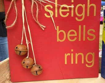 Sleigh Bells Ring sign with rusty bells