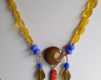 Necklace in shades of yellows, oranges and lilacs.