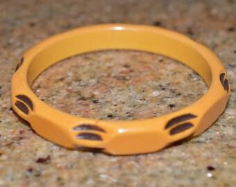 Butterscotch carved bakelite over dyed bakelite bangle bracelet