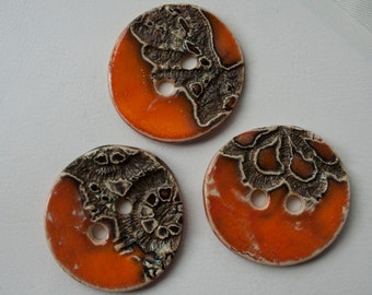3 orange ceramic buttons with a reflection mosaic