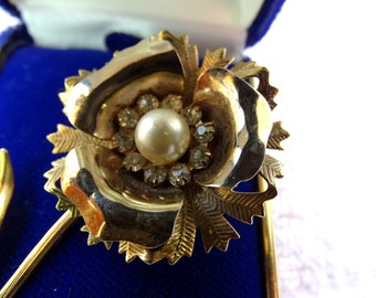 Flower brooch .Gold tone flower with a pearl and clear prong set rhinestones