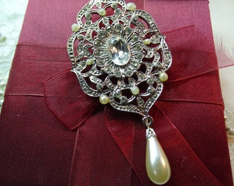 Silver tone brooch. Large filigree rhinestone and faux pearl brooch.Intricate and stylish.