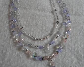Multi strand necklace of pale purple and pink and clear beads