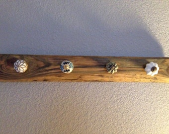Reclaimed barn wood scarf/jewlery rack with assorted decorative knobs. Stain and knob color optional.