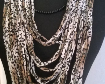 Tshirt Scarf with print in the colors: creamy white, black, beige, sand and something green and 2 loose long black bead necklaces