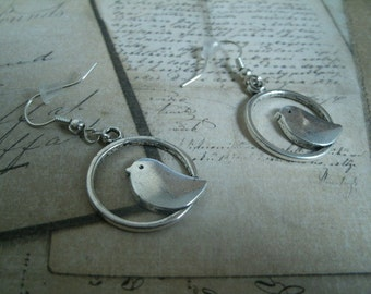Earrings representing a bird in  silver color metal