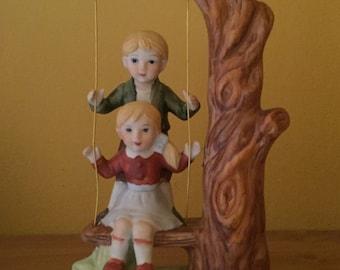 Vintage boy & girl on a swing