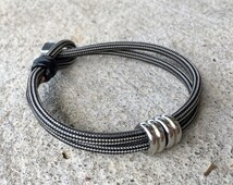 Mens Bracelet, Pattern Color Choice, Paracord, Black Leather Wrap, Loop and Hex Nut Closure, Stainless Steel Cylinder Beads