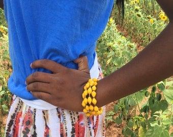 Yellow paper bead bangle handmade in Uganda.