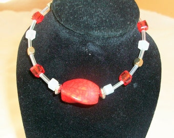 Red beaded bracelet with feature bead
