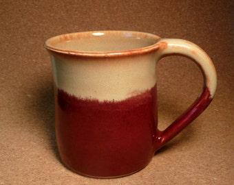 Stoneware mug in deep red, creamy tan