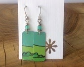 Earrings made from recycled goat cheese can.