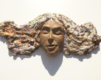 Ceramic wall hanging face sculpture, textured glazes, wild hair portrait art, figure mask painting