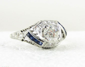 Edwardian Platinum Diamond Engagement Ring, Old European Cut Diamond in Filigree Setting with Sapphire Accents, Circa 1910s.