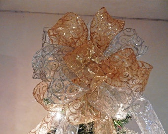 Large Christmas Tree topper bow made with a sheer gold ribbon with gold glitter swirls and sheer silver with silver glitter swirls