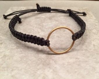 Simple center circle gold tone statement bracelet knotted black adjustable sizing