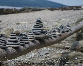 Rock Cairns on Driftwood with Ocean and Mountains in background - Photograph