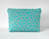 Woman's floral seedling print padded travel bag cosmetics make up pouch flowers in aqua blue green and white.