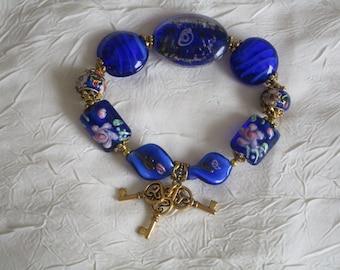 Bracelet en perles lampwork bleues avec breloques clefs.
