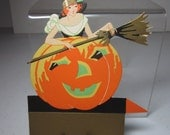 1920's-30's unused Gibson die cut gold gilded halloween place card pretty witch standing over jack o'lantern holding a broom