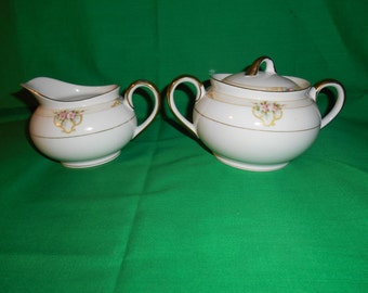 One (1), Porcelain Sugar Bowl With Lid and Creamer, from Noritake, in: The Vitry Pattern.