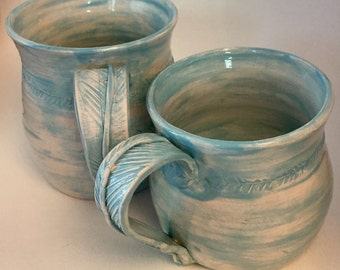 Pair of Light Blue Wheel Thrown Migs with Feather Handle and Distresses Glaze