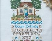 Completed unframed primitive cross stitch Beach cottage sampler