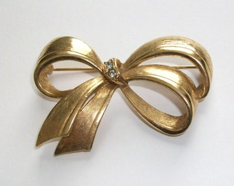 "Pretty Avon golden bow pin with rhinestones to wear on your jacket. About 2 1/4"" wide and 1 1/2"" tall."