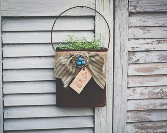 Tin wall pocket! Burlap accent with a cream rosette. Little bird nest accent with a paper tag bird cage! Filled with paper grass!